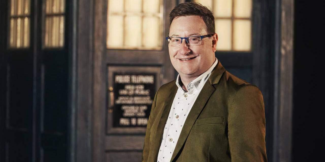 Uśmiechnięty Chris Chibnall na tle TARDIS.
