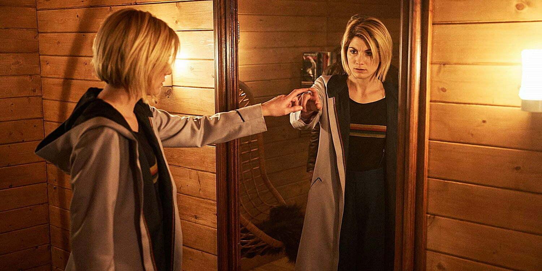 Trzynasta Doktor dotyka palcem lustra na ścianie wyłożonego jasnymi drewnianymi panelami pokoju. W odbiciu widać, że jest zaniepokojona.