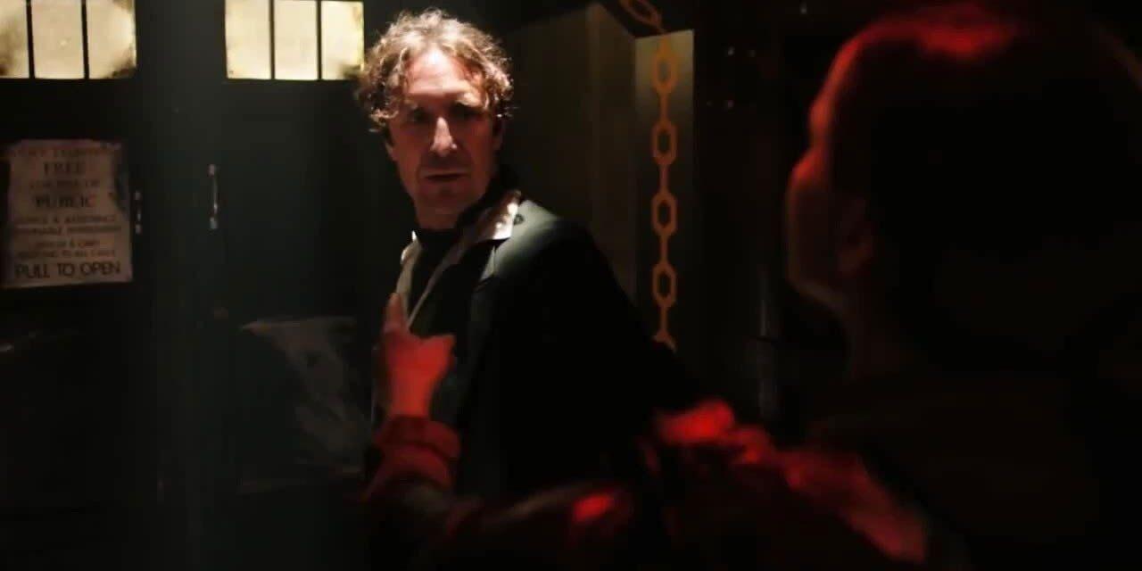Kadr z miniodcinka Noc Doktora. Ósmy Doktor stoi przed poobijaną TARDIS patrząc na stojącą przed nim rozmaraną sylwetkę Cass, która wskazuje TARDIS.