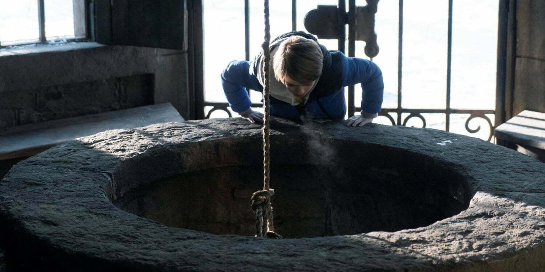 """Kadr z serialu """"Locke & Key"""". Bode po raz pierwszy zagląda do studni."""
